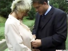 mature lady younger guy play around in the grass
